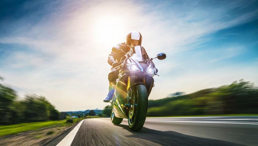 Biker riding motorcycle on road against sky