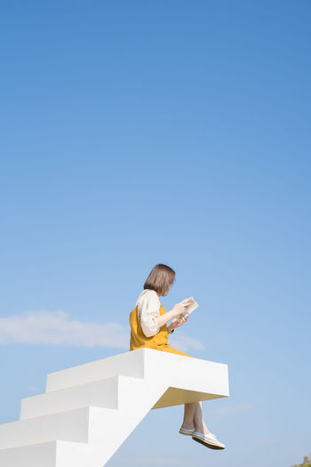 Low angle view of woman sitting on steps while reading book against sky