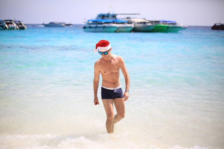 Shirtless Man Wearing Santa Hat While Wading In Sea Against Sky
