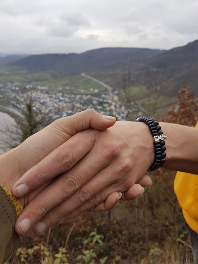 Cropped image of friends holding hands against mountains