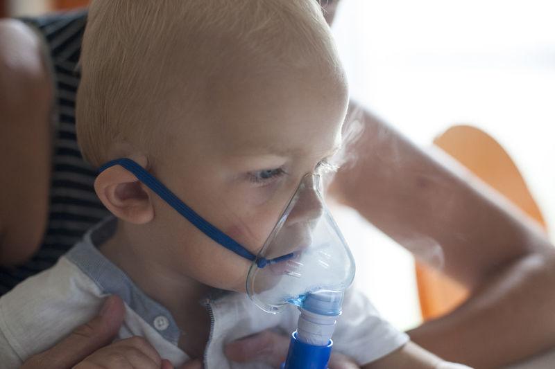 Close-up portrait of boy on inhalator