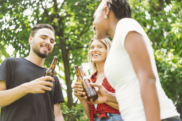friends talking and toasting beers outdoors. Party people drinks toast celebration. Beer Beer - Alcohol Beer Glass Beers Drink Bottle Celebration Celebrating Celebrate BBQ BBQ Time Outdoors Park Garden Barbecue Barbecue Grill Grill Grilled Grilling African African Ethnicity Asian  Friendship Smiling Happiness Emotion Young Adult Young Women Togetherness Leisure Activity Lifestyles Men Casual Clothing Women Fun Group Of People Adult Waist Up Holding Enjoyment Positive Emotion Drinking Glass