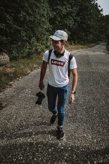 Full length of young man walking on road