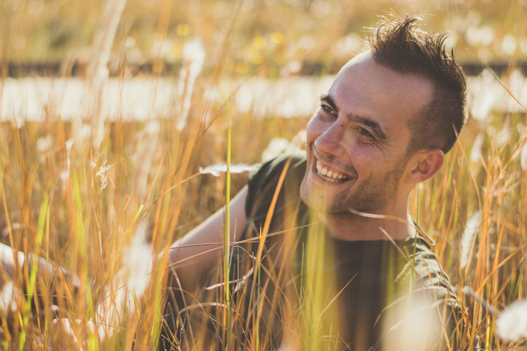 Smiling man sitting amidst plants on field during sunny day