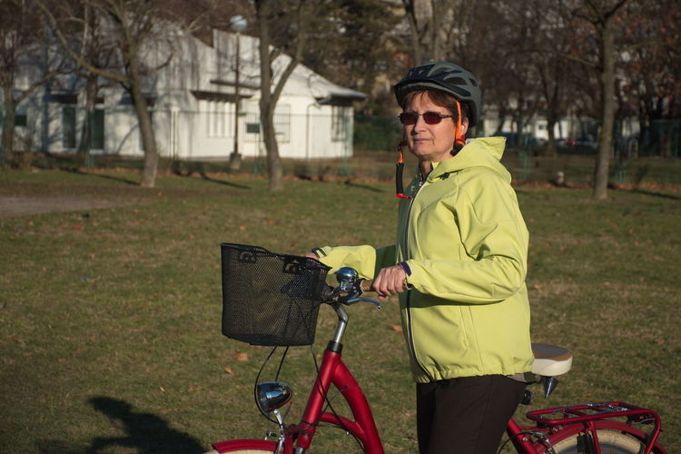 One Person Real People Tree Lifestyles Plant Land Clothing Leisure Activity Standing Day Field Nature Bicycle Grass Focus On Foreground Transportation Outdoors Warm Clothing Mode Of Transportation Yellow Basket Helmet Activity Glasses Eyeglasses  Red Citybike Park House Riding Bike