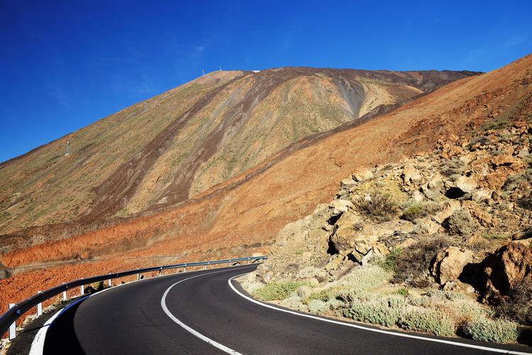 Empty Road Along Rocky Landscape Against Blue Sky