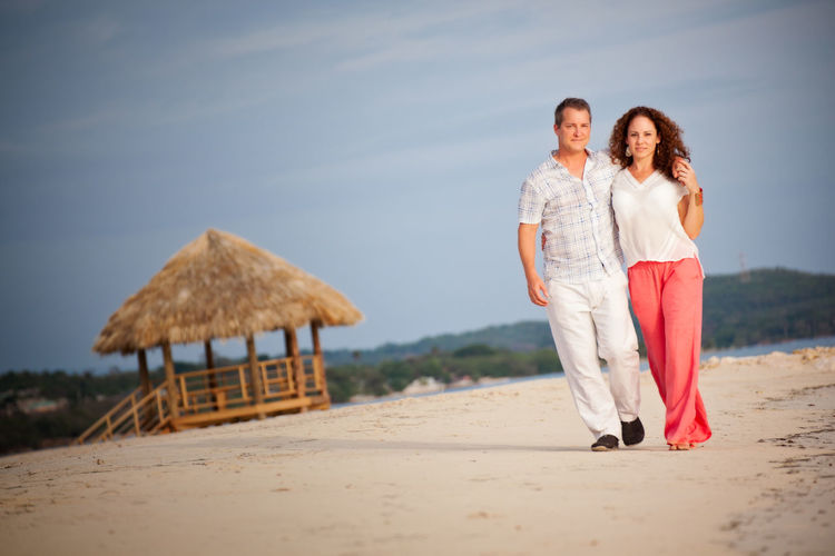 Full length of mature couple walking at beach