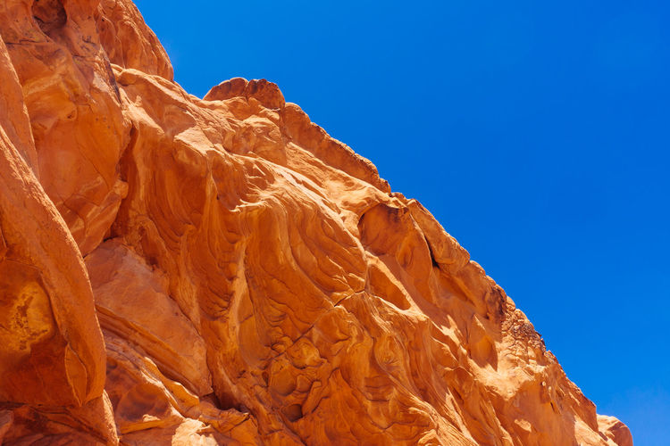 Close-up of rock against clear blue sky