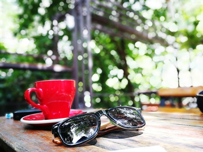 Close-Up Of Tea Cup And Sunglasses On Table