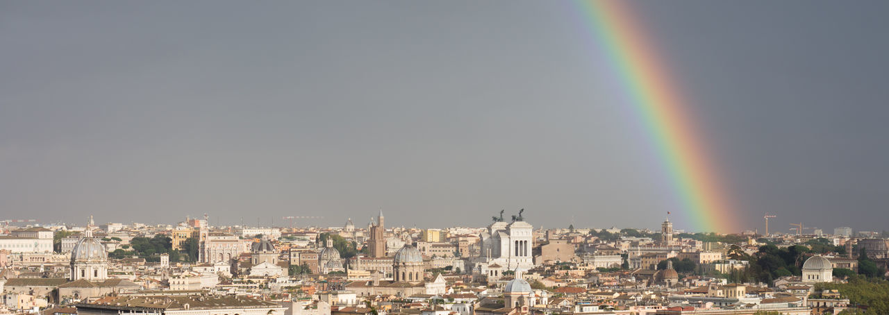 Rainbow over city buildings against sky