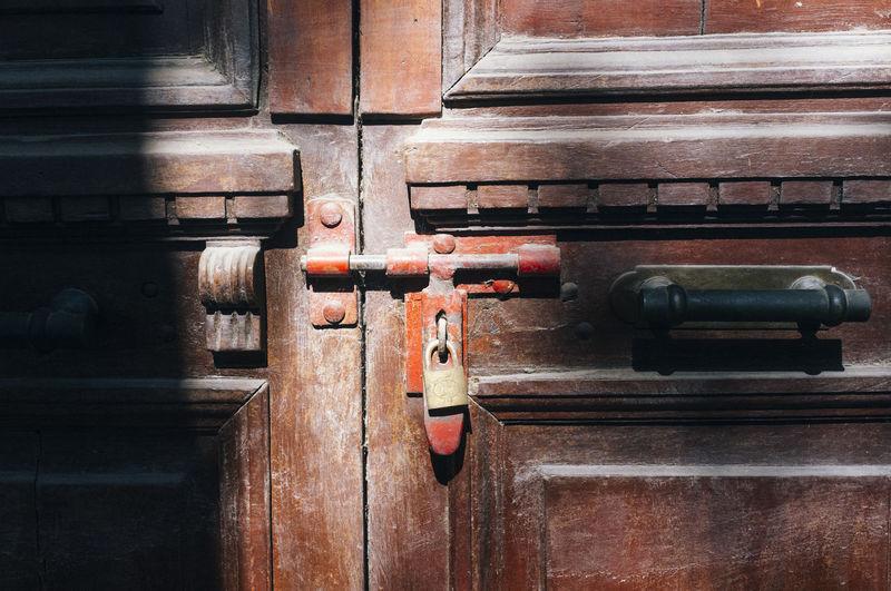 Close-Up Of Padlock Hanging On Wooden Door