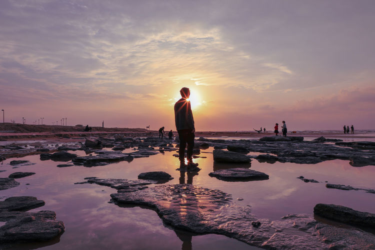 Silhouette of young man standing at beach against sky during sunset