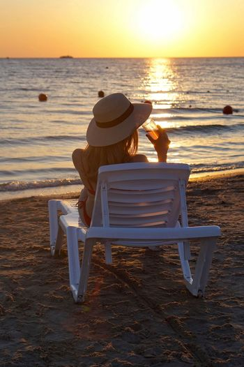 Rear view of woman relaxing on lounge chair at beach during sunset