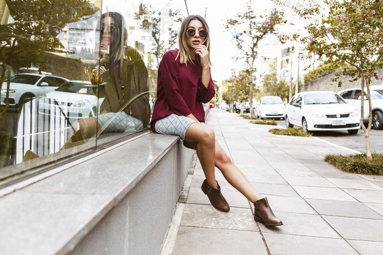 Portrait Of Young Woman Sitting On Sidewalk By Glass Building