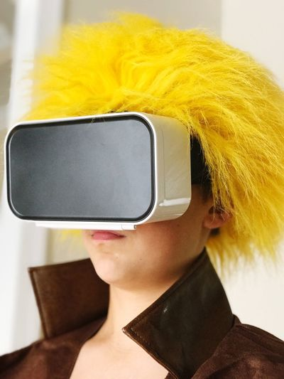 Close-up of woman with dyed hair wearing virtual reality simulator