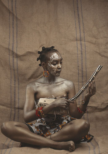 High angle view of eastafrican woman sitting on the floor with music instrument