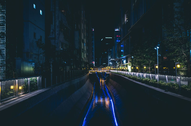 Illuminated River Amidst Buildings In City At Night
