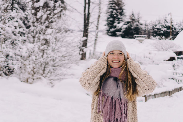 Portrait of smiling woman on snow covered land