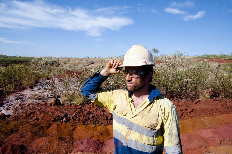 Miner wearing hardhat standing on field