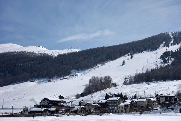 Scenic view of snow covered landscape and houses against sky