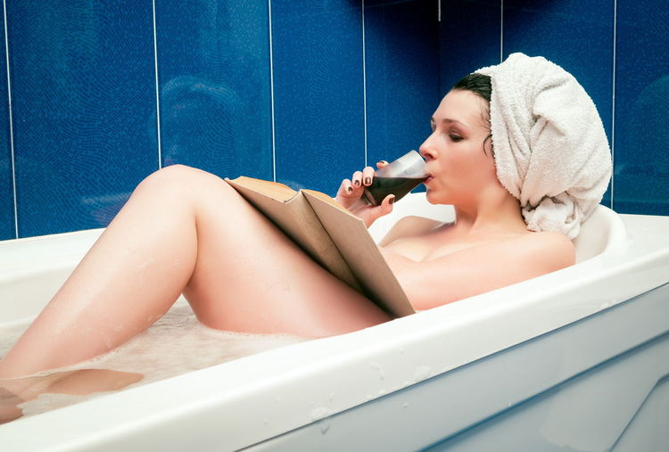 Naked woman with wine reading book while sitting in bathtub