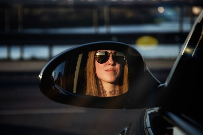 Woman wearing sunglasses while looking out of car window