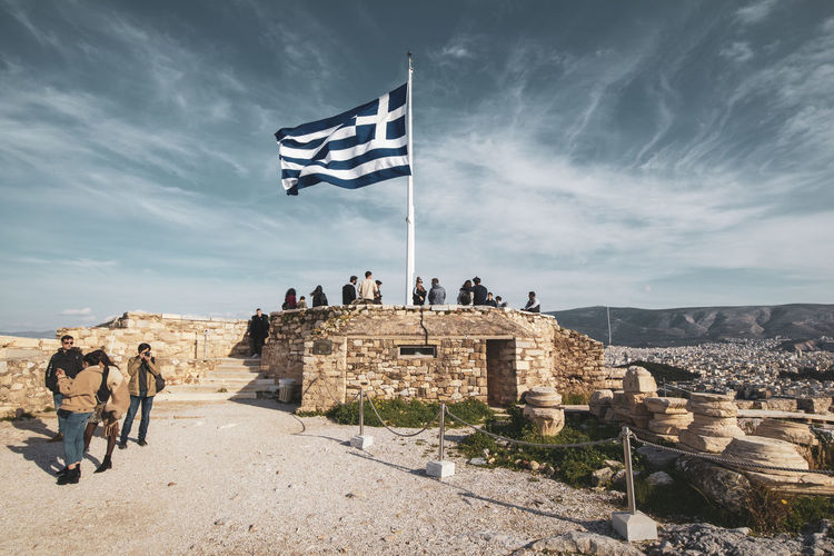Acropolis Athens Greece Acropolis Architecture Sky History The Past Flag Cloud - Sky Group Of People Built Structure Patriotism Real People Building Exterior Nature Men Travel Destinations Ancient Day Travel Tourism Lifestyles Ancient Civilization Outdoors Wind Archaeology Stone Wall