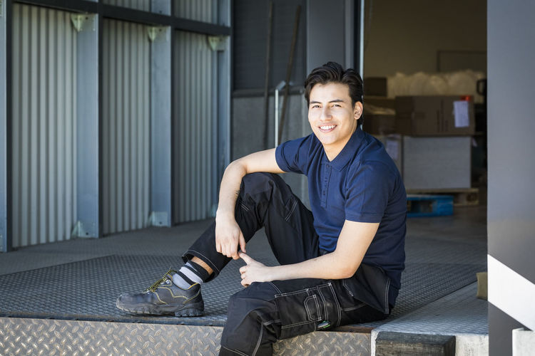 Portrait of a smiling young man sitting outdoors