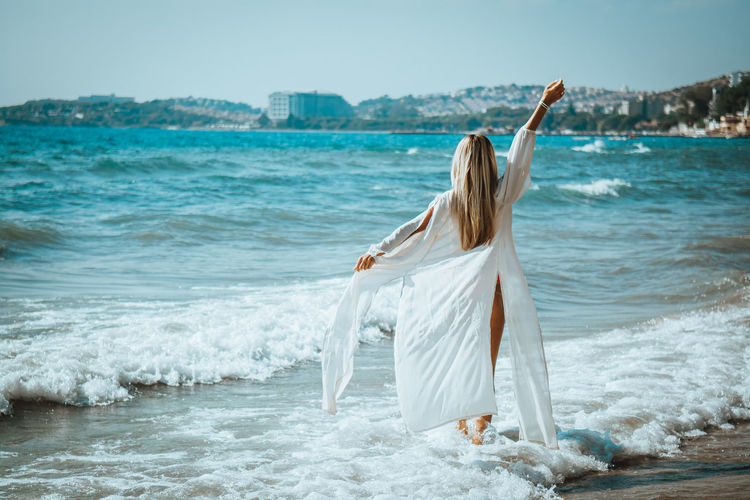 Woman wearing shirt while wading in sea