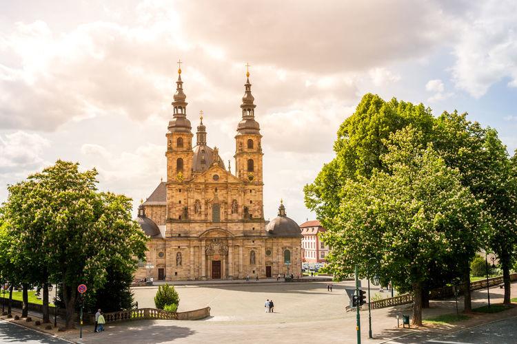 Historic church in city against cloudy sky