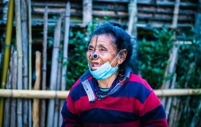 Senior woman wearing mask looking away while standing outdoors