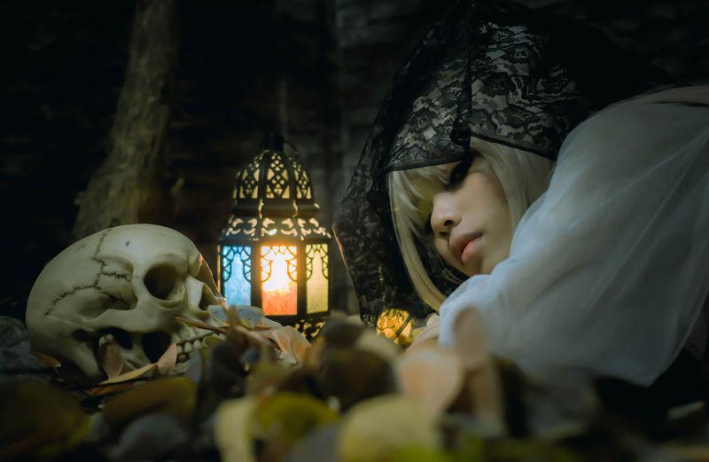 Portrait of woman wearing halloween costume lying on leaves