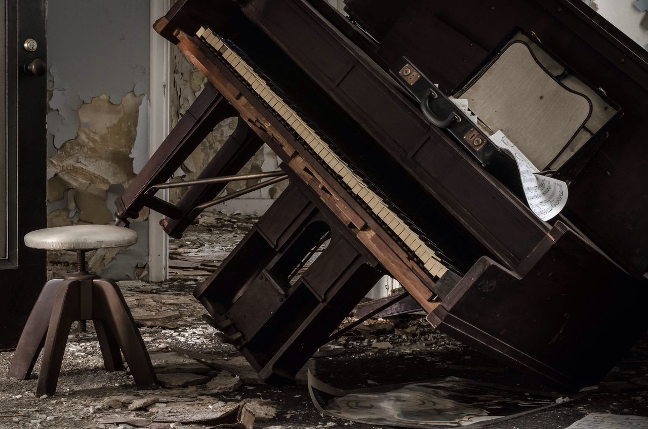 A smashed piano in a wrecked room
