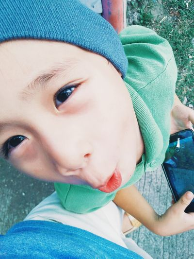 High angle view of cute boy making face