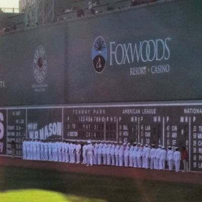 Sailors and officers posted before the Green Monster at Myfenway