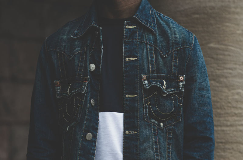 Midsection Of Person Wearing Denim Jacket