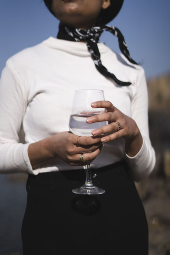 Midsection of woman holding glass outdoors