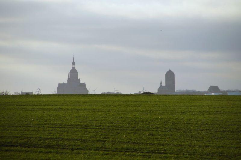 Church on field against cloudy sky