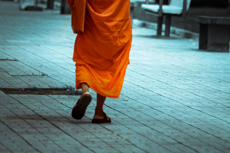 Low section of man wearing orange traditional clothing walking on footpath