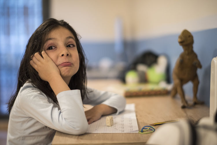Girl making face while studying at table