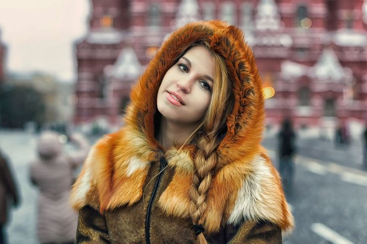 Portrait Of Beautiful Woman In Warm Clothing Standing On City Street