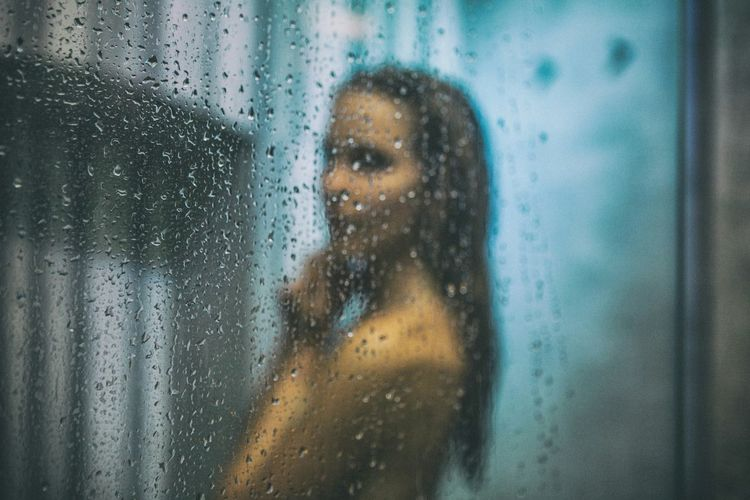 Side View Of Young Woman Bathing In Bathroom Seen Through Glass