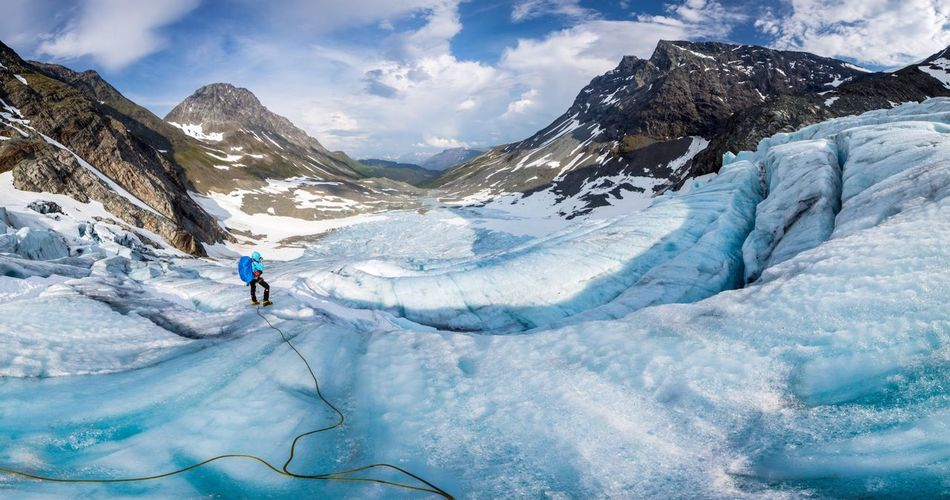 High angle view of woman hiking downhill on glacier against sky