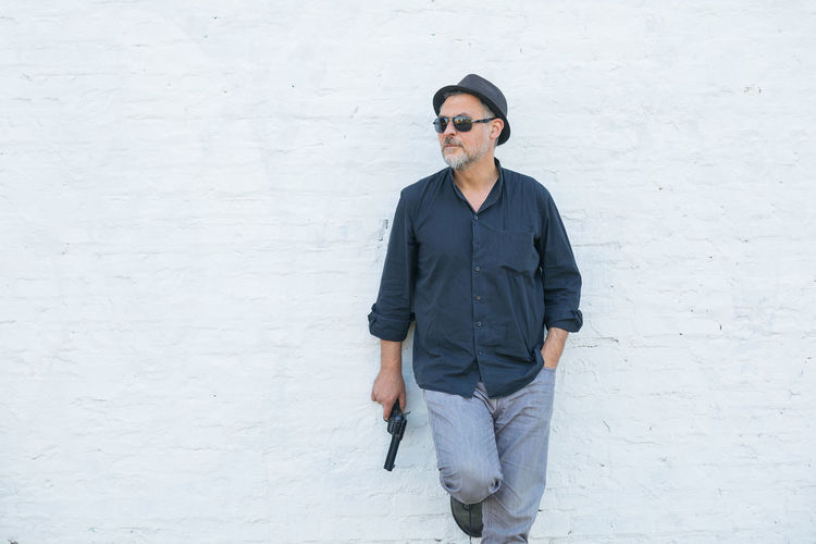 Man wearing sunglasses holding gun against white wall
