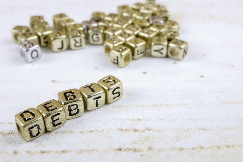 DEBT CONCEPT WITH GOLD DICE ON A WOODEN TABLE Arts Culture And Entertainment Capital Letter Close-up Communication Credit Card Debt Crisis High Angle View Indoors  Large Group Of Objects Leisure Games Letter No People Number Still Life Studio Shot Table Text Toy Western Script White Color Wood - Material