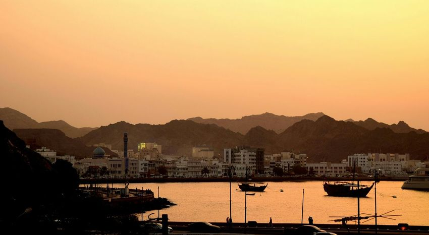 The end of a day, sun sets behind the Alhajar mountains in Muscat .. The buildings, the mosque and the dhow in the ocean await a starlit night over Mutrah corniche..Sunset Silhouettes Mutrah Muscat , Oman Mosque Corniche End Of The Day Mountains AwaitingNightfall