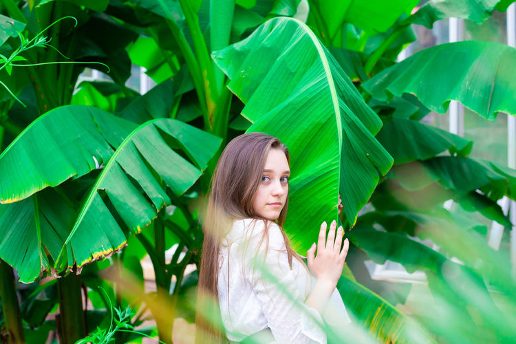 Portrait of young woman standing by banana leaf outdoors
