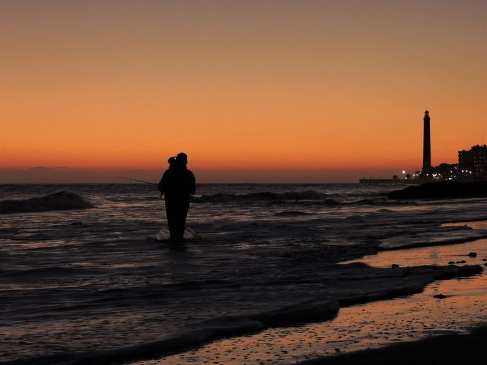 Silhouette Man Standing In Sea Against Clear Sky During Sunset