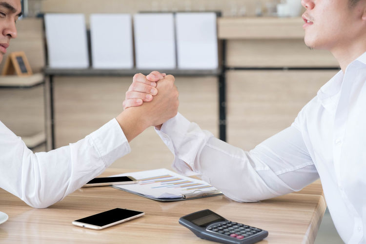 Close-Up Of Businessmen Arm Wrestling On Table In Office