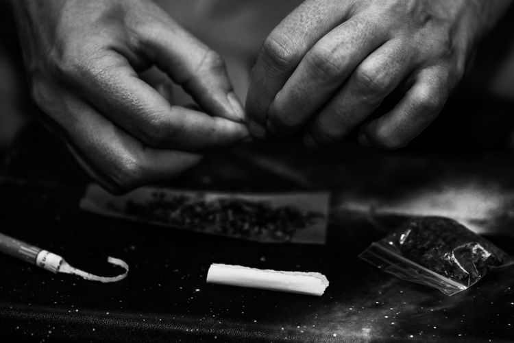 Cropped hand of woman making marijuana joint on table